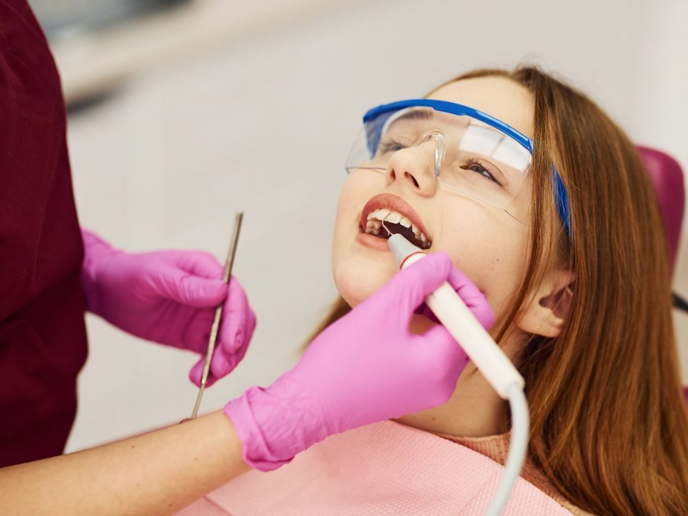 Little girl in protective glasses visiting dentist in clinic. Conception of stomatology