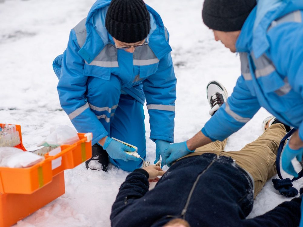 Two contemporary paramedics giving first aid to sick unconscious man outdoors